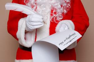 bigstock-Santa-Claus-holding-a-quill-pe-39548263